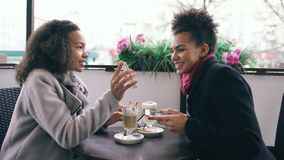 Two attractive mixed race female friends sharing together using smartphone in street cafe outdoors. Two attractive mixed race female friends sharing together Stock Photos