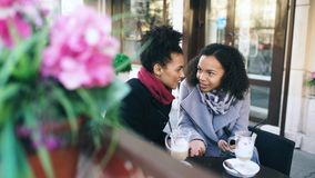 Two attractive mixed race female friends sharing together using smartphone in street cafe outdoors. Two attractive mixed race female friends sharing together Stock Images