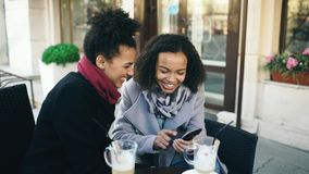 Two attractive mixed race female friends sharing together using smartphone in street cafe outdoors. Two attractive mixed race female friends sharing together Royalty Free Stock Photos