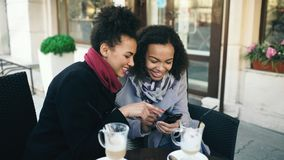 Two attractive mixed race female friends sharing together using smartphone in street cafe outdoors. Two attractive mixed race female friends sharing together Stock Photo