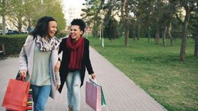 Two attractive mixed race women dancing and have fun while walking down the park with shopping bags. Happy young friends. Two attractive mixed race women dancing royalty free stock photography
