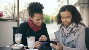 Two attractive mixed race women having online shopping with credit card and smartphone while talking and drinking coffee stock video