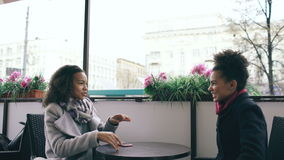 Two attractive mixed race women meet in cafe hugging and sitting together stock video footage