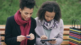 Two attractive mixed race women with paper bags sitting on bench and using tablet computer and credit card for online. Internet shopping stock video footage