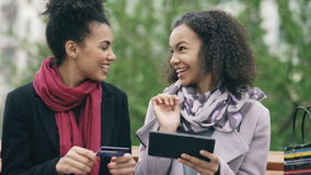Two attractive mixed race women with paper bags sitting on bench and using tablet computer and credit card for online stock video