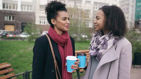 Two attractive mixed race women with shopping bags drinking coffe and talking at the street. Young girls smiling and stock footage