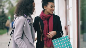 Two attractive mixed race women with shopping bags surpisely meet on the street near mall store stock video footage