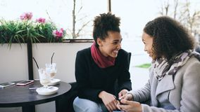 Two attractive mixed race women talking and drinking coffee in street cafe. Friends have fun after visiting mall sale. S stock photography