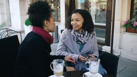 Two attractive mixed race women talking and drinking coffee in street cafe. Friends have fun after visiting mall sale Stock Photography
