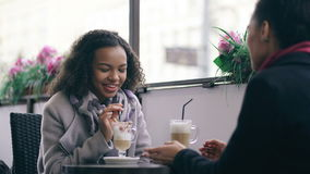 Two attractive mixed race women talking and drinking coffee in street cafe. Friends have fun after visiting mall sale stock footage