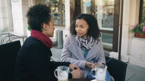 Two attractive mixed race women talking and drinking coffee in street cafe. Friends have fun after visiting mall sale stock video