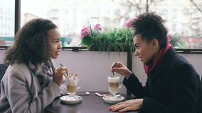 Two attractive mixed race women talking and drinking coffee in street cafe. Friends have fun after visiting mall sale stock video footage