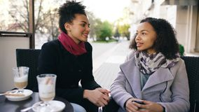 Two attractive mixed race women talking and drinking coffee in street cafe. Friends have fun after visiting mall sale Royalty Free Stock Image