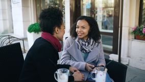 Two attractive mixed race women talking and drinking coffee in street cafe. Friends have fun after visiting mall sale Royalty Free Stock Photos