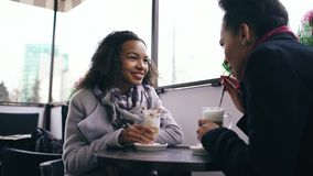 Two attractive mixed race women talking and drinking coffee in street cafe. Friends have fun after visiting mall sale Stock Images