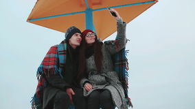 Two attractive people, covered with a blanket, make selfie against the gray sky. Girl in a red cap and glasses, and a guy in a gray coat posing for a selfie stock footage