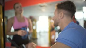 Two attractive people getting acquainted in gym, sport uniting hearts, flirt. Stock footage stock footage