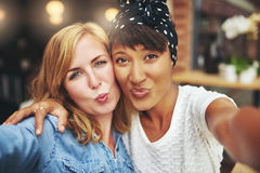 Two attractive playful women blowing a kiss Stock Image