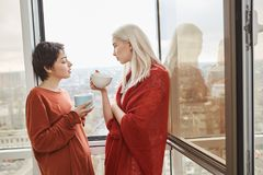 Two attractive and sensual girlfriends standing near opened window in red clothes while drinking coffee.  Royalty Free Stock Photo