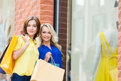 Two attractive shopaholics posing near store window Royalty Free Stock Photos