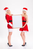 Two attractive sisters twins standing and holding blank board Stock Images