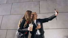 Two attractive smiles Caucasian girls taking selfie photos on smartphone near gray wall. Outdoor. People, friends and stock footage