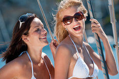 Two attractive smiling woman on sailboat Stock Photos
