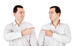Two attractive smiling young men twins showing at each other Stock Photos