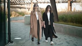Two attractive street fashion stars walking in autumn street. Blonde and brunette young women in stylish clothes and sunglasses are walking in autumn street stock footage