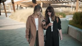 Two attractive street fashion vloggers walking in autumn street. Blonde and brunette young women in stylish clothes and sunglasses are walking in autumn street stock footage
