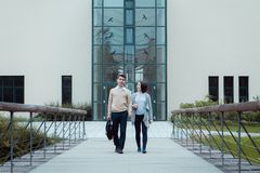 Two attractive students friends walking on campus road. Smart students men and women student walking outdoor Stock Images