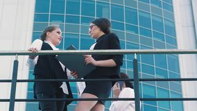 Two attractive stylish female coworkers chatting outdoors during time off stock video footage