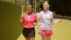 Two attractive stylish tennis players walking. Two attractive stylish young women tennis players walking along a curving drive chatting and smiling as they make stock footage