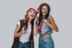 Two attractive stylish young women. Laughing while standing against grey background stock photo
