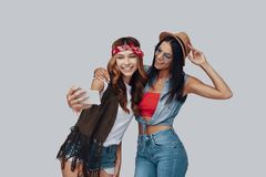 Two attractive stylish young women. Taking selfie and smiling while standing against grey background stock photography