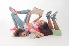 Two attractive teen girls are reading Stock Image