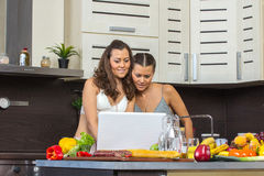 Two attractive twins women looking at laptop, standing in kitche Stock Image