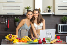 Two attractive twins women looking at laptop, standing in kitche Stock Photography