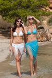 Two attractive woman in bikini on the beach Stock Photos