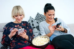 Two attractive woman friends with mobile phone and popcorn Royalty Free Stock Photo