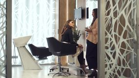 Two attractive woman looking on each other and speak in spa. Two brunette hair woman speaking in bright and light room on coffee break. They spending time stock video