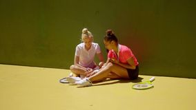 Two attractive woman tennis players relaxing. Two attractive trendy young woman tennis players relaxing in the sunshine sitting on the ground in front of a stock video footage