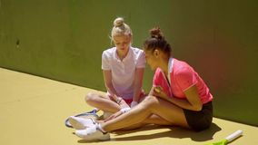 Two attractive woman tennis players relaxing. Two attractive trendy young woman tennis players relaxing in the sunshine sitting on the ground in front of a stock footage