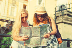 Two attractive woman tourists looking at the map in the city. Va Stock Photography