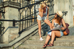 Two attractive woman tourists looking at the map in the city. Vacation concept.Summer vacation. Stock Photography