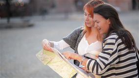 Two attractive woman tourists traveling on holidays in city smiling happy. Girls with city map in search of attractions stock video footage