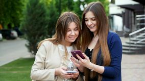 Two attractive woman use mobile phones, looking a photo, game, application, shopping. Two attractive woman use mobile phones, looking a photo, game, application stock video footage