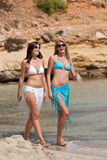 Two attractive woman walking on the beach Stock Photos
