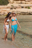 Two attractive woman walking on the beach Stock Photo