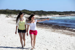 Two attractive woman walking on a beach Stock Photo